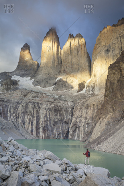 A trekker admires a stormy sunrise near a glacial pool below the iconic Torres