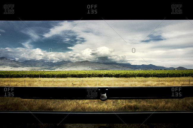 View of the vineyards and mountains in distance, from a moving train near Podgorica, Montenegro