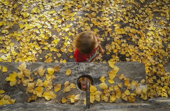 Baby girl playing with water in the fountain in a autumn scape