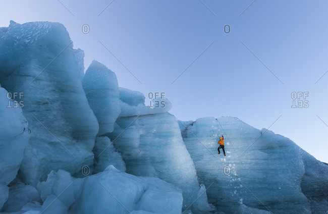 Man climbing a steep glacier ice in Gigjokull South Iceland