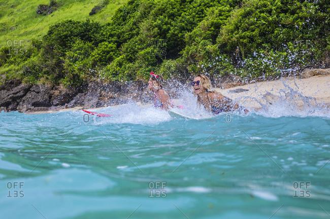 Surfer girls in ocean water