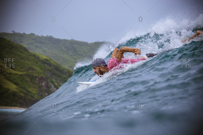 Surfer in Indian ocean near the coastline of Lombok island, Indonesia