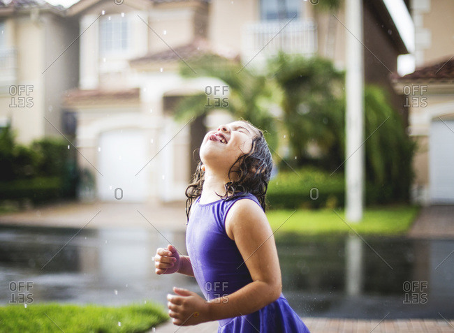 A little girl sticks out her tongue in the rain