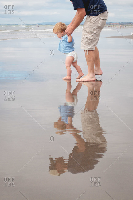 Father walking with his son on the beach