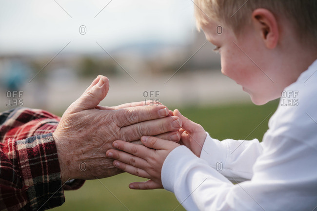 Young boy touching the hands of his grandparent