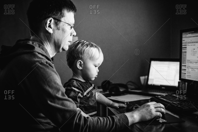 Father working on a computer with his son
