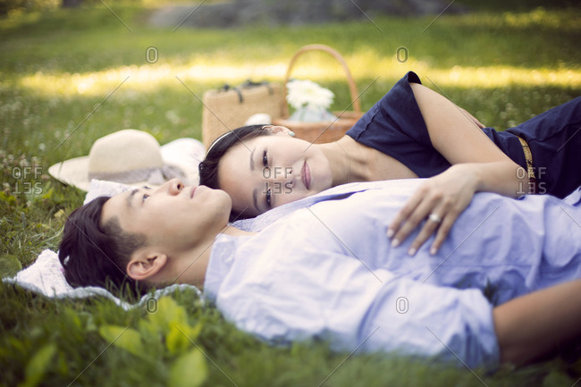 Affectionate young couple lounge on a picnic blanket on the grass