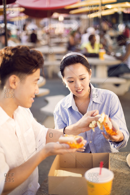 Couple enjoying hot dogs at outdoor table