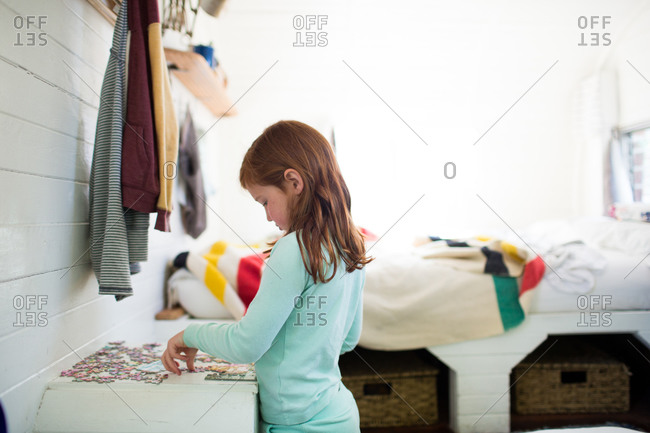 Girl putting together a puzzle on small table