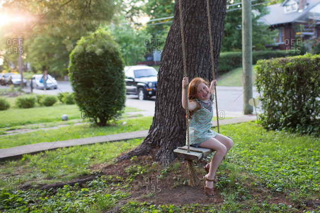 Girl sitting on rope swing at dusk