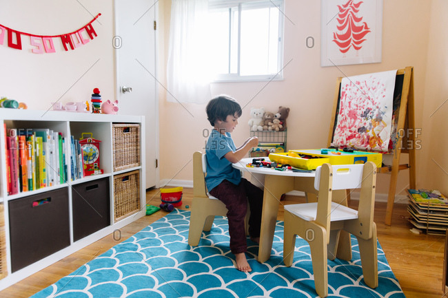 A boy plays with building blocks in his home