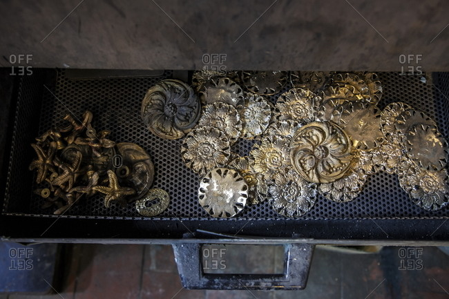 Brass handles and decorative accessories in a drawer at a furniture accessory shop