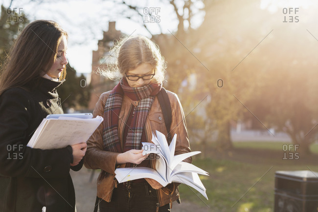 Two college students looking through textbook outdoors