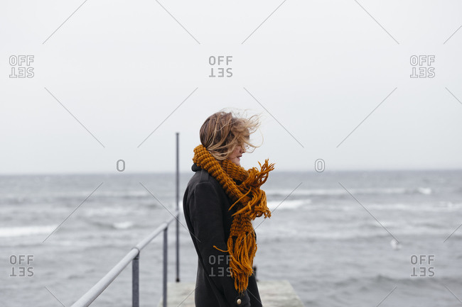 Young woman standing on dock on choppy water
