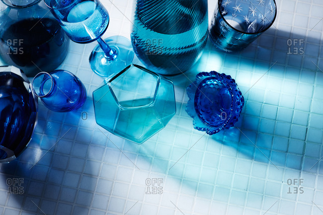 Blue glassware on a white tile floor