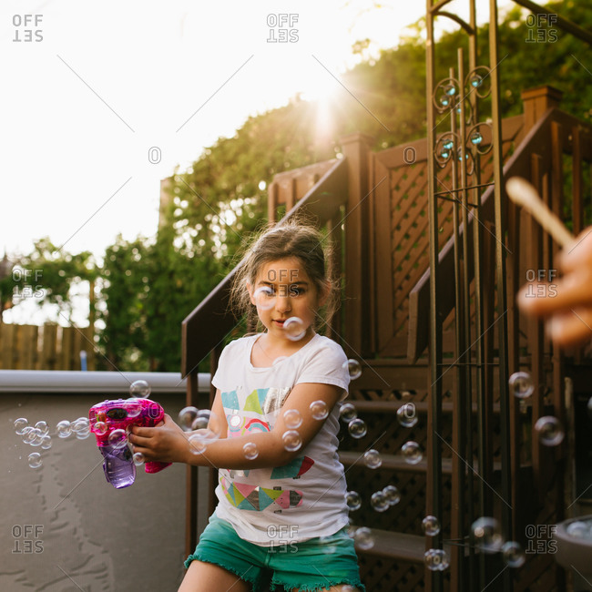 Girl playing with a bubble gun
