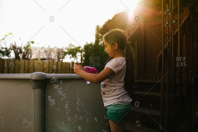 Young girl playing with a bubble gun