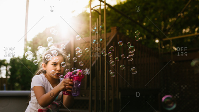 Girl playing with a bubble gun toy