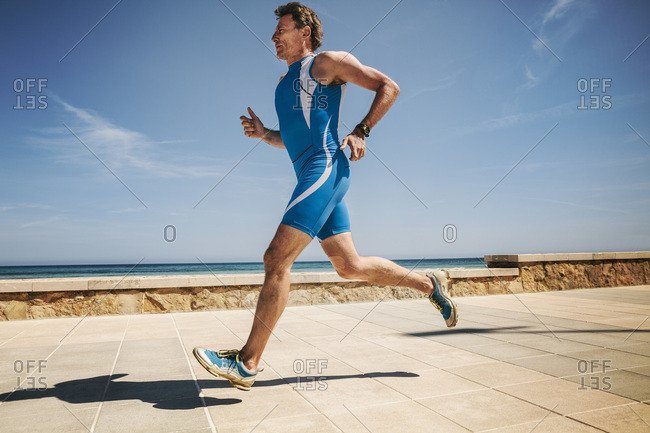 Triathlete running along beach promenade