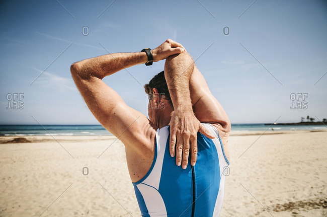 Back view of triathlete stretching on the beach