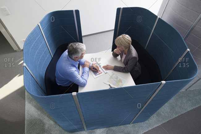 Businessman and businesswoman working in partitioned board room
