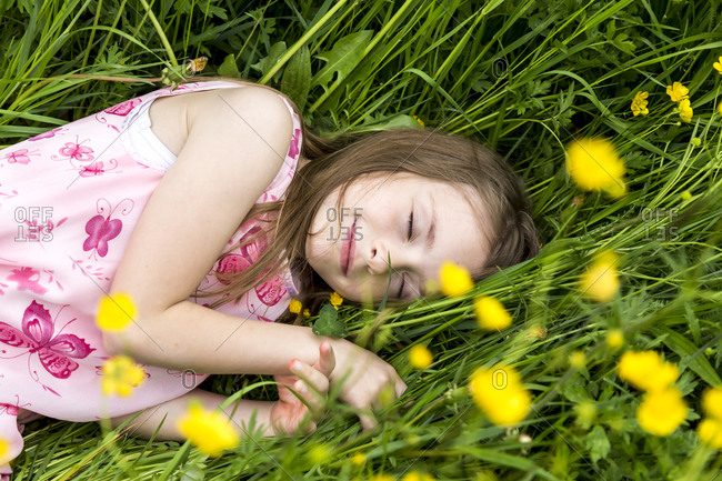 Smiling little girl with closed eyes lying on a flower meadow