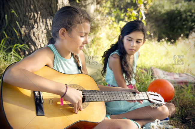 Girl in meadow playing guitar with sister watching