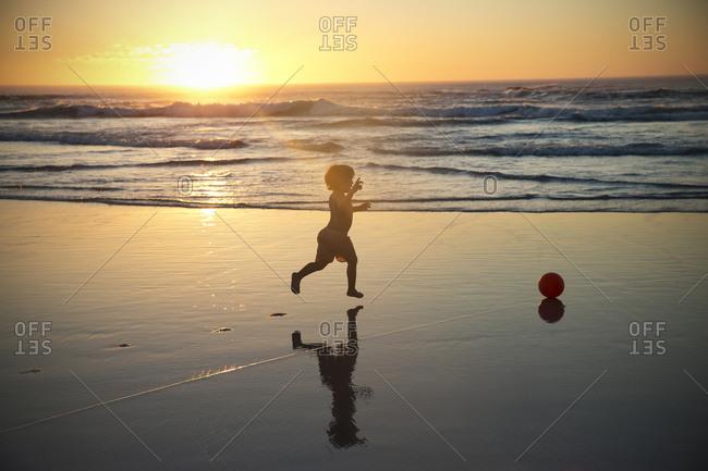 Boy running on beach at sunset