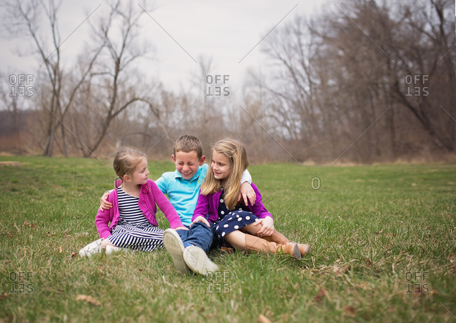Three siblings sitting on the grass