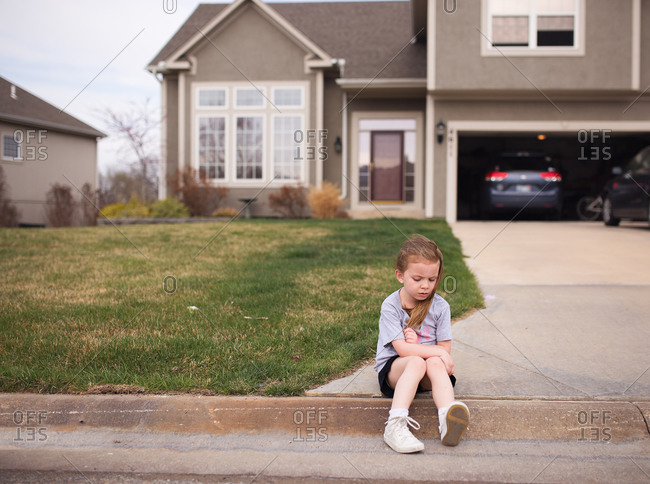 Sad girl sitting on the curb