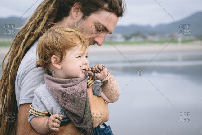 Man holding his toddler as he eats sand