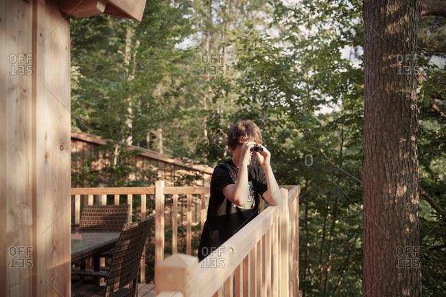 Boy looking through binoculars from a tree house