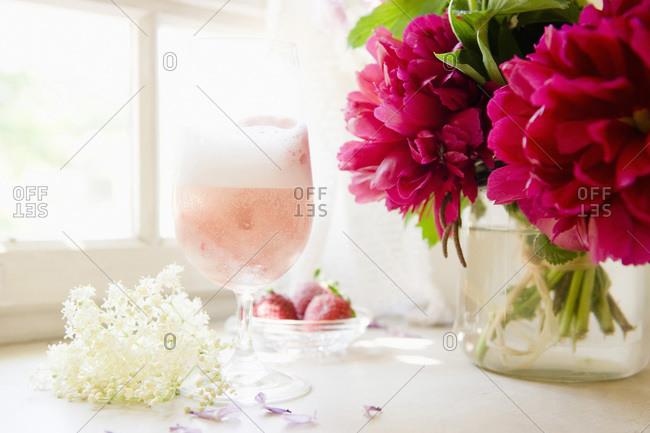 Sparkling wine with elderflower blossom and strawberries
