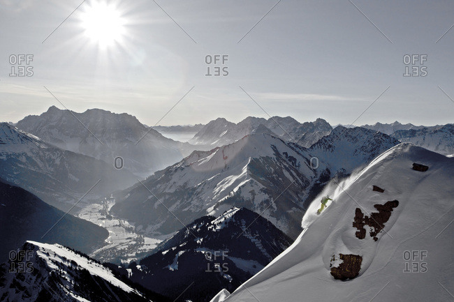 Person snowboarding in deep powder snow in the Thaneller mountains, Tyrol, Austria
