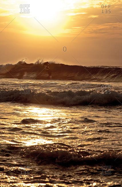 Surfer riding a wave at the coast of Praia, Santiago, Cape Verde