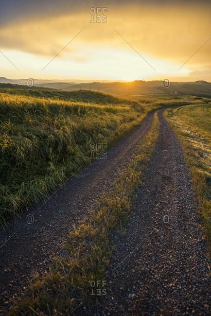 May 30, 2014: Dirt road at sundown nearby Pienza in Siena, Tuscany, Italy