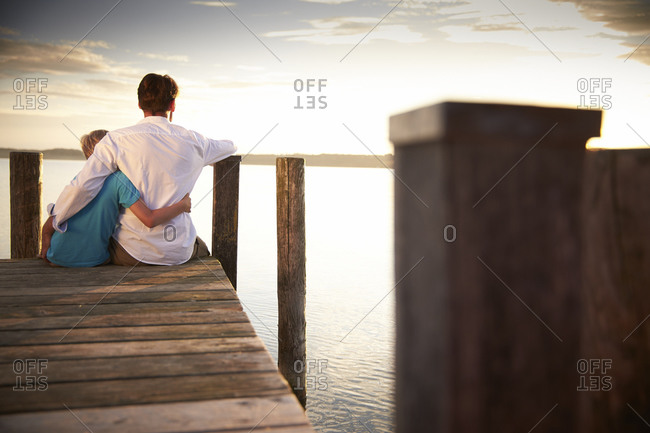 Father relaxing with his son on pier at Lake Starnberg in Bayern, Germany