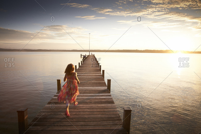 Young girl running on pier at Lake Starnberg in Bayern, Germany