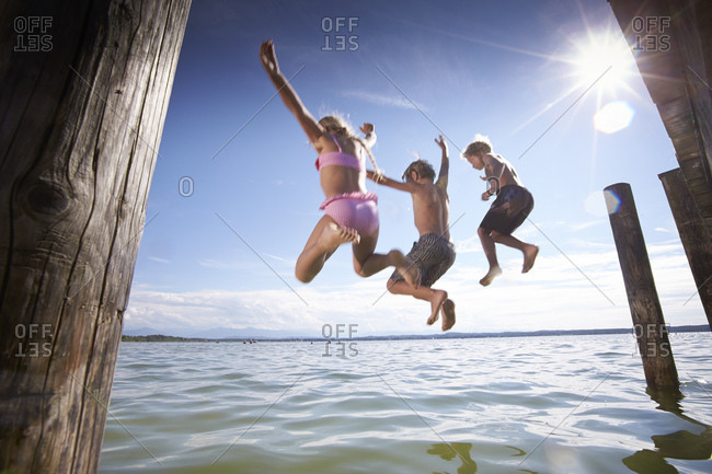 Children jumping together into the Starnberg lake in Bayern, Germany