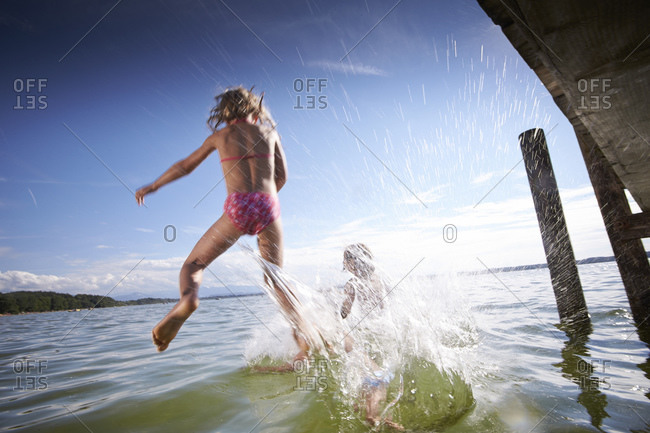 Children jumping into the Starnberg lake in Bayern, Germany
