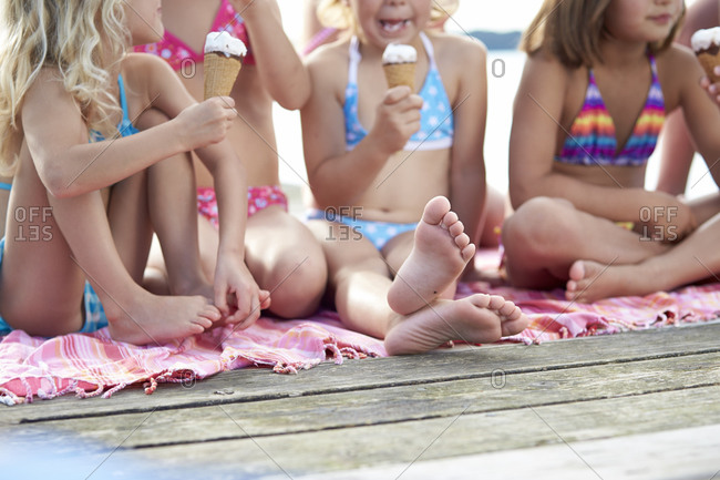Young girls eating ice creams on a pier at Starnberg lake in Bayern, Germany