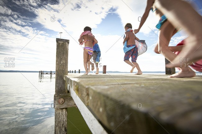 Children running on a jetty at the Starnberg lake in Bayern, Germany