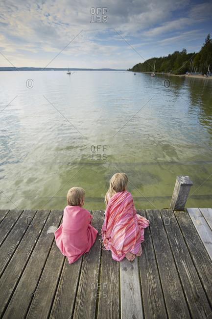 Children relaxing on pier at Lake Starnberg in Bayern, Germany