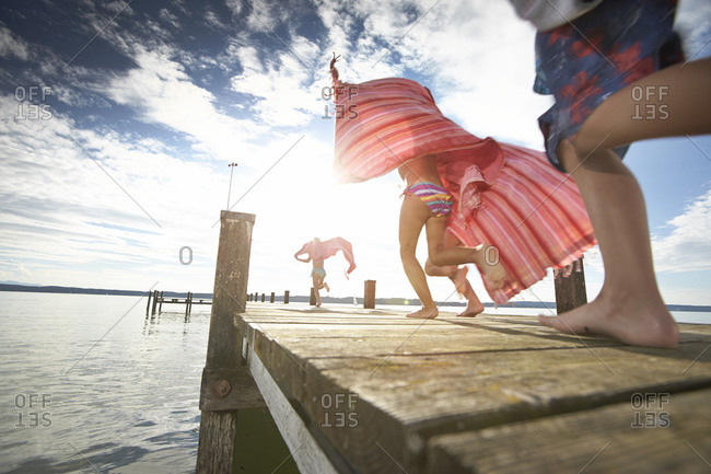 Children running on a pier at the Starnberg lake in Bayern, Germany