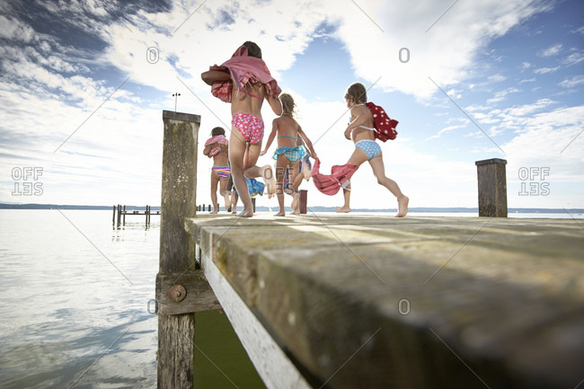 Girls running on a jetty at the Starnberg lake in Bayern, Germany