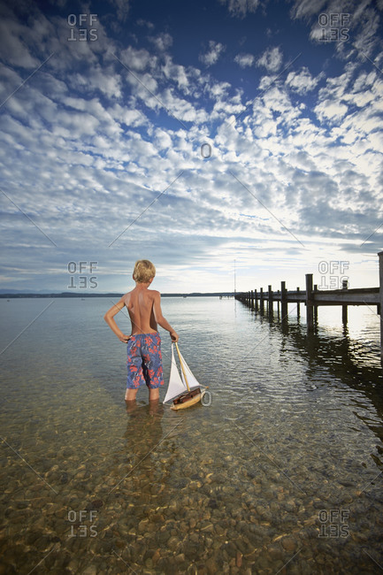 Young boy with a toy boat standing in Lake Starnberg, Bayern, Germany