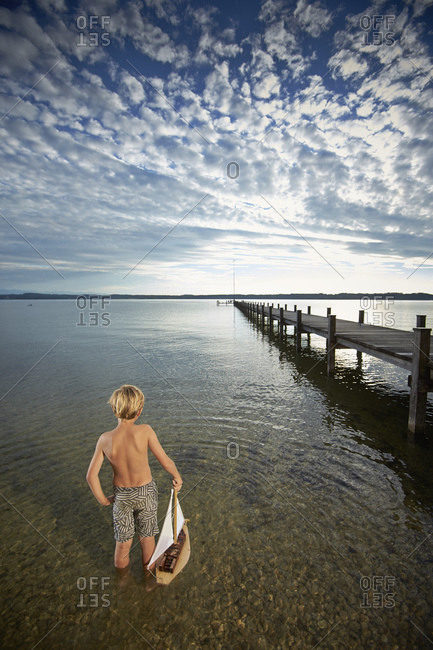 Blonde boy with a toy sailboat standing in lake Starnberg, Bayern, Germany