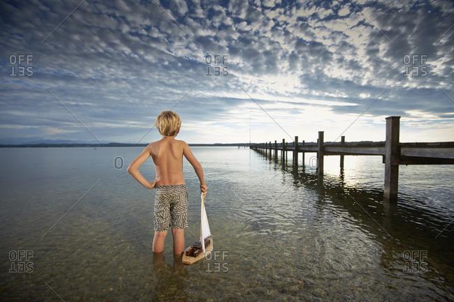 Blonde boy holding a toy sailboat in lake Starnberg, Bayern, Germany
