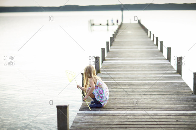 Young girl crouching on a pier at Lake Starnberg in Bayern, Germany