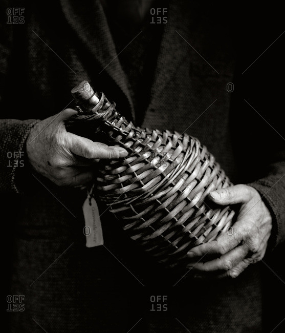 Man holding a wicker bottle